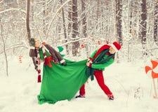 Junge Paare, Mann und Frau, Ehemann und Frau gehen in Kostüme von den Blumen, die von den Elfen von Sankt-` s Helfern typisch sin stockfoto