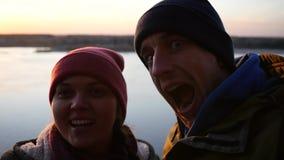 Junge Paare, Mann und Frau machen ein Foto am Telefon und lachen über die Kamera auf einem Sonnenunterganghintergrund durch den F stock video