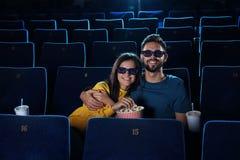 junge Paare mit aufpassendem Film des Popcorns im Kino lizenzfreie stockfotografie