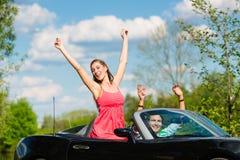 Junge Paare mit Cabriolet im Sommer am Tag lösen aus Stockfotografie