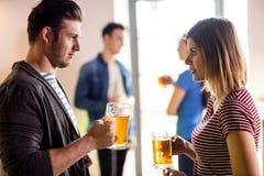 Junge Paare mit dem Bierkrug in der Bar Stockfoto