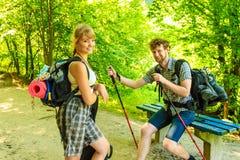 Junge Paare mit dem Gitarrenrucksack wandern im Freien Stockfoto