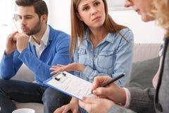 Junge Paare mit dem Psychologefamilientherapietherapeuten, der Kenntnisse nimmt lizenzfreie stockfotos