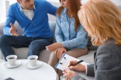 Junge Paare mit dem Psychologefamilientherapietherapeuten, der medizinische Form schreibt lizenzfreie stockfotografie