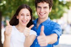 Junge Paare mit den Daumen oben Lizenzfreie Stockbilder