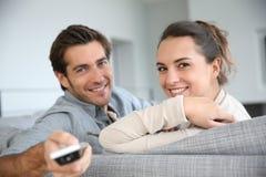 Junge Paare mit der Fernbedienung, die auf Sofa sitzt Stockfotografie