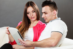 Junge Paare mit der Tablette, die zu Hause auf Couch sitzt Stockfotografie