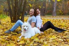 Junge Paare mit einem Hund im Herbstwald Lizenzfreies Stockfoto