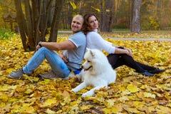 Junge Paare mit einem Hund im Herbstwald Lizenzfreie Stockbilder