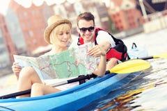 Junge Paare mit einer Karte in einem Kanu Stockfotografie