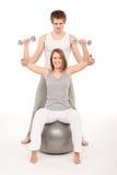 Junge Paare mit Gewichten, Eignungkugel auf Weiß stockbild