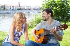 Junge Paare mit Gitarre draußen Lizenzfreie Stockfotos