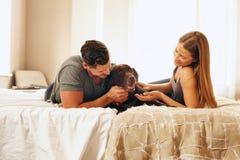Junge Paare mit ihrem Hund auf dem Bett am Morgen Stockbild
