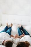 Junge Paare mit kleinem Kind auf weißem Bett Das Kind betrachtet die Kamera Stockfotos