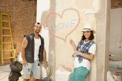 Junge Paare mit Liebe simsen geschrieben auf Wand stockfotos