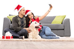 Junge Paare mit Sankt-Hüten, die ein selfie nehmen Stockfotos