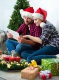 Junge Paare mit Santa Claus-Hüte kaufendem on-line-Weihnachtsgif Stockbilder