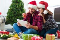 Junge Paare mit Santa Claus-Hüte kaufendem on-line-Weihnachtsgif Stockfotos