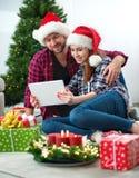 Junge Paare mit Santa Claus-Hüte kaufendem on-line-Weihnachtsgif Stockfotografie