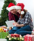 Junge Paare mit Santa Claus-Hüte kaufendem on-line-Weihnachtsgif Stockbild