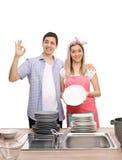 Junge Paare mit Stapeln des sauberen okayzeichens der Plattenherstellung Lizenzfreie Stockfotos