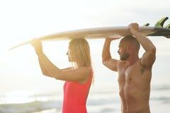 Junge Paare mit Surfbrett draußen Stockbilder