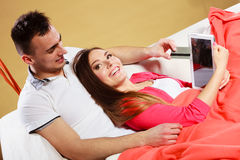 Junge Paare mit Tablette und Kreditkarte zu Hause Stockfotografie