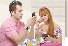 Junge Paare mit Telefonen auf Weiß Lizenzfreies Stockfoto