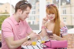 Junge Paare mit Telefonen in einer Kaffeestubeterrasse Lizenzfreie Stockbilder