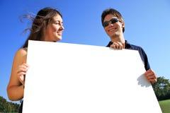 Junge Paare mit unbelegtem Zeichen lizenzfreie stockfotografie