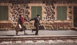 Junge Paare mit Weinlesekoffer auf den trainlines bereit zu a lizenzfreie stockfotografie