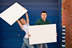 Junge Paare mit Zeichen 1 Stockfotografie