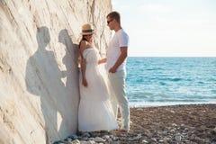 Junge Paare nahe dem Felsen auf der Seeküste lizenzfreie stockbilder