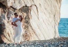 Junge Paare nahe dem Felsen auf der Seeküste lizenzfreie stockfotos