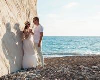 Junge Paare nahe dem Felsen auf der Seeküste stockfotos