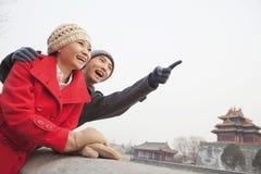 Junge Paare in Peking im Winter, zeigend weg vom Schirm Stockfoto