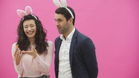 Junge Paare sind auf rosa Hintergrund schön Während dieser Zeit werden sie in den Mobohren gekleidet Betrachten einander stock video footage