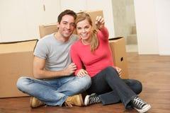 Junge Paare sitzen auf der Fußbodenholdingtaste in der Hand Lizenzfreies Stockbild