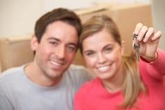Junge Paare sitzen auf der Fußbodenholdingtaste in der Hand Stockbilder