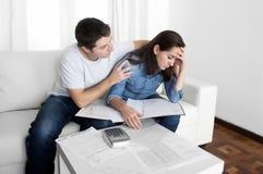 Junge Paare sorgten sich nach Hause im Druckehemann, der Frau in den Finanzproblemen tröstet Lizenzfreie Stockfotografie