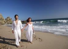 Junge Paare am Strandgehen Lizenzfreies Stockbild