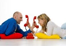 Junge Paare am Telefon Lizenzfreie Stockbilder