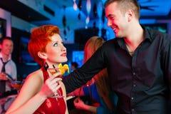 Junge Paare in trinkenden Cocktails des Stabes oder des Klumpens Stockbilder