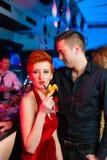 Junge Paare in trinkenden Cocktails des Stabes oder des Klumpens Lizenzfreie Stockfotos