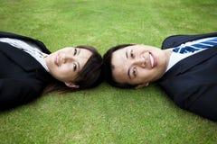 Junge Paare und Lage auf dem Gras Lizenzfreie Stockfotografie