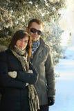 Junge Paare unter Tannenbäumen Stockfotos