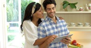 Junge Paare unter Verwendung der digitalen Tablette in der Küche stock video footage