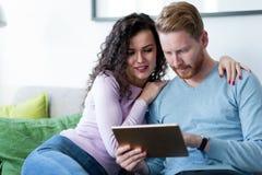 Junge Paare unter Verwendung der digitalen Tablette zu Hause Stockbild