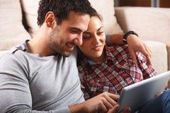 Junge Paare unter Verwendung der Tablette stockfotografie