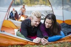 Junge Paare unter Verwendung des Handys im Zelt Lizenzfreies Stockbild